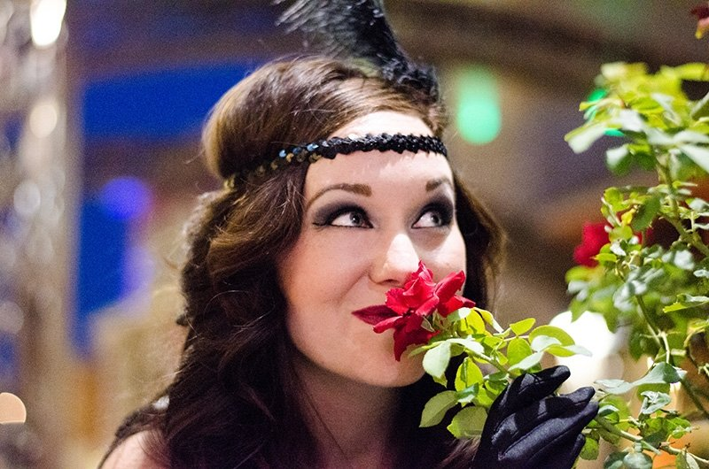 Jenny taking time to smell the roses during a 1920s photo shoot of a flapper girl with Black Door Media